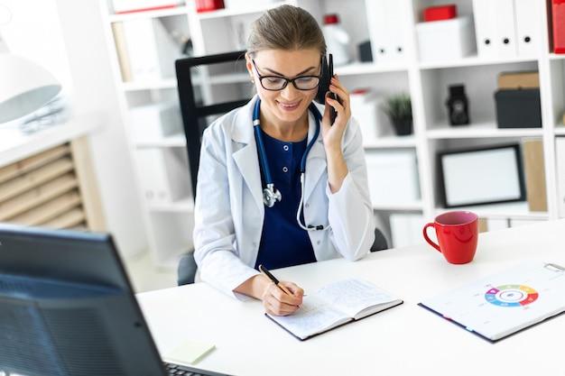 Uma jovem garota com uma túnica branca está sentada na mesa do escritório, falando ao telefone e segurando uma caneta na mão. um estetoscópio está pendurado no pescoço.