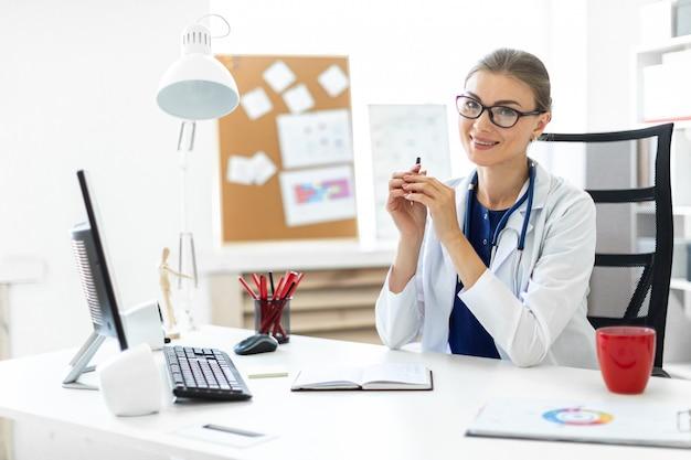 Uma jovem garota com uma túnica branca se senta às mesas no escritório e segura uma caneta na mão.