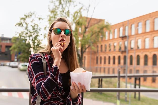 Uma jovem garota come batatas fritas na rua.