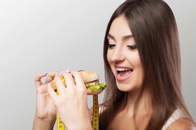 Uma jovem garota come um hambúrguer e pensa em uma dieta. emagrecimento redefina o excesso de peso. o conceito de saúde e beleza.