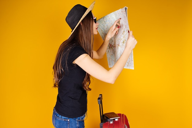 Uma jovem garota de cabelo comprido com um chapéu saiu em uma aventura, nas férias, olha para o mapa