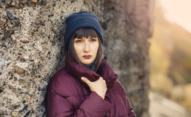 Uma jovem garota de chapéu azul e jaqueta misteriosamente desvia o olhar.