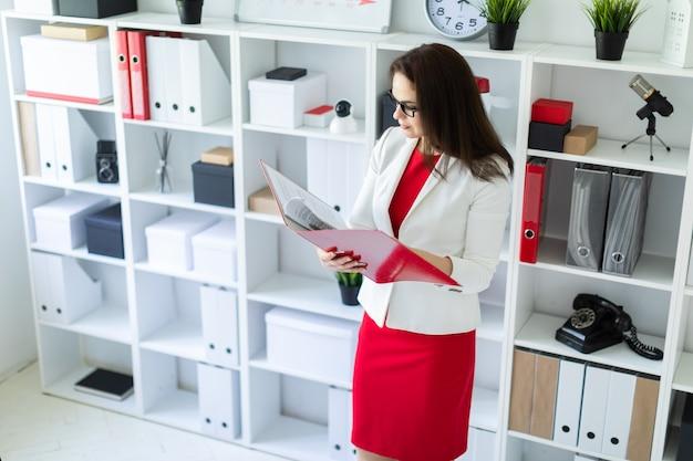 Uma jovem garota de pé no escritório perto da mesa e segurando uma pasta com documentos.