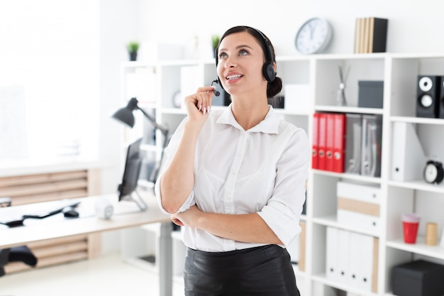 Uma jovem garota em fones de ouvido com microfone está em um escritório brilhante.