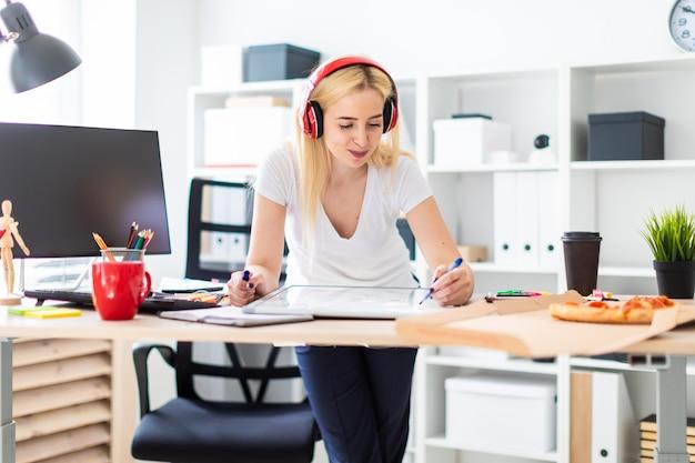 Uma jovem garota em fones de ouvido fica perto da mesa e tem um marcador na mão. em cima da mesa está um quadro magnético.
