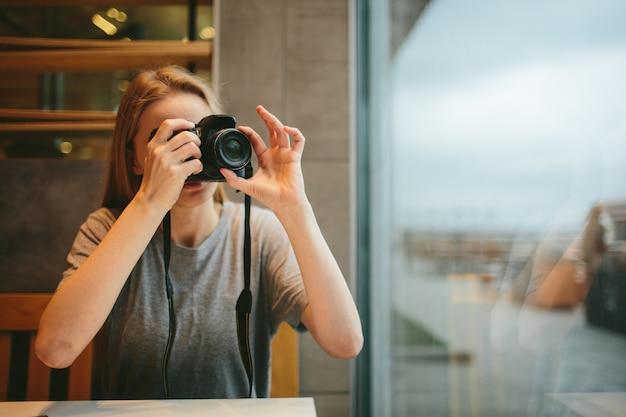 Uma jovem garota em um café tira fotos com a câmera