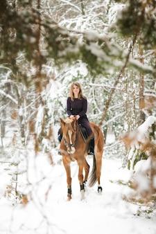 Uma jovem garota em um vestido cavalga por um bosque nevado em um cavalo. passeios a cavalo no inverno.