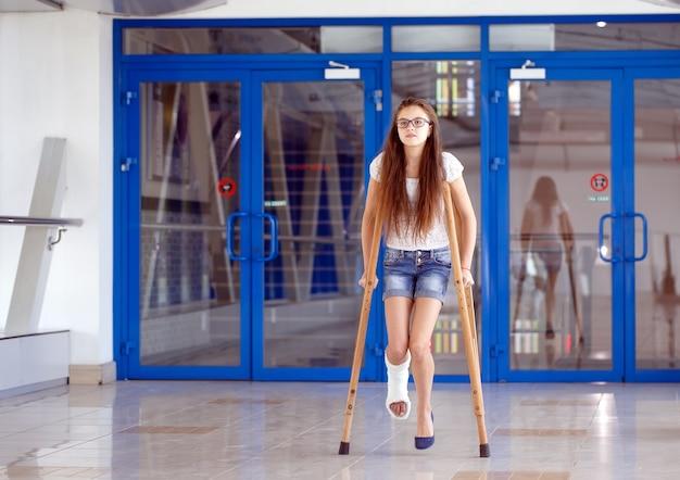 Uma jovem garota está de muletas no corredor do hospital.