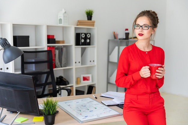 Uma jovem garota está de pé encostado em uma mesa e segurando um copo vermelho nas mãos.