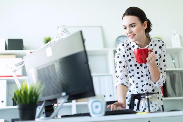 Uma jovem garota está de pé no escritório perto da mesa, segurando uma caneca vermelha na mão e digitando no teclado.