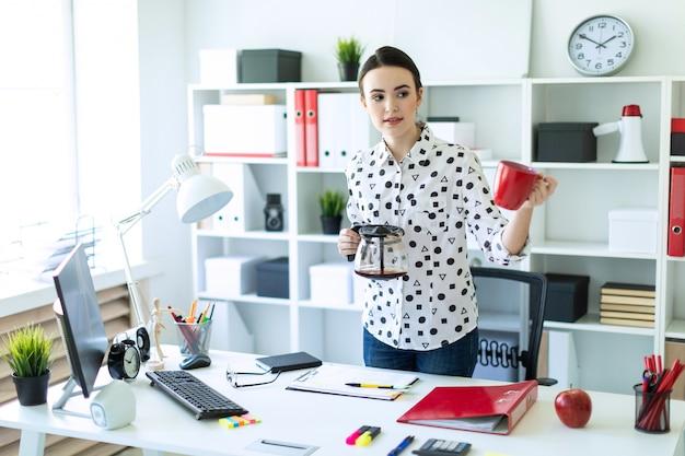 Uma jovem garota está de pé no escritório perto da mesa, segurando uma chaleira na mão e segurando um copo.