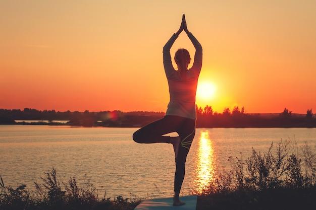 Uma jovem garota está de pé no lago ao pôr do sol, fazendo yoga.