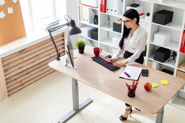 Uma jovem garota está de pé perto da mesa e digitando o texto no teclado.