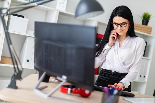 Uma jovem garota está de pé perto da mesa, falando ao telefone e digitando no teclado.