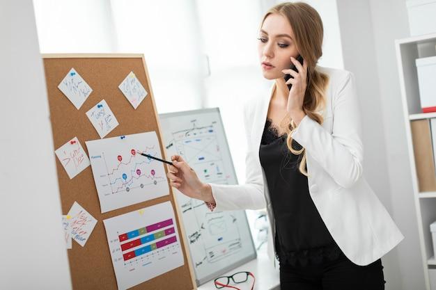 Uma jovem garota está de pé perto da placa com adesivos, falando ao telefone e segurando um lápis na mão.