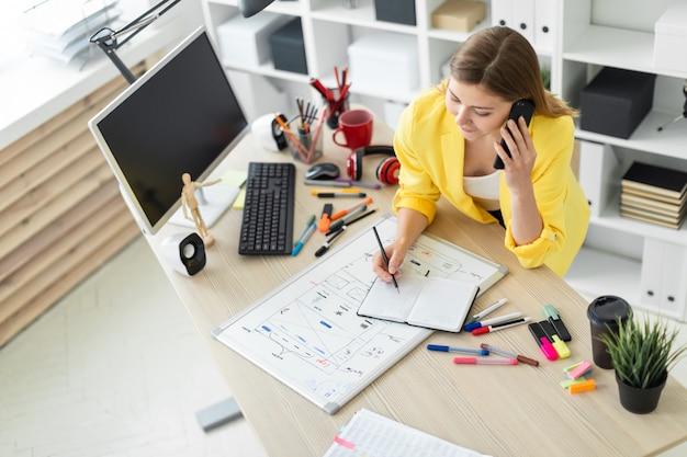 Uma jovem garota está de pé perto de uma mesa, falando ao telefone, segurando um lápis na mão e fazendo anotações