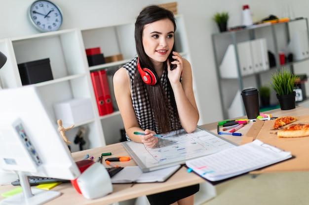 Uma jovem garota está de pé perto de uma mesa, segurando um marcador verde na mão e falando ao telefone.