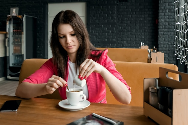 Uma jovem garota está derramando creme ou leite no café em um café na mesa de madeira