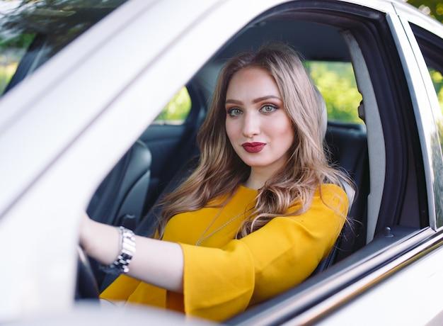 Uma jovem garota está dirigindo um carro.
