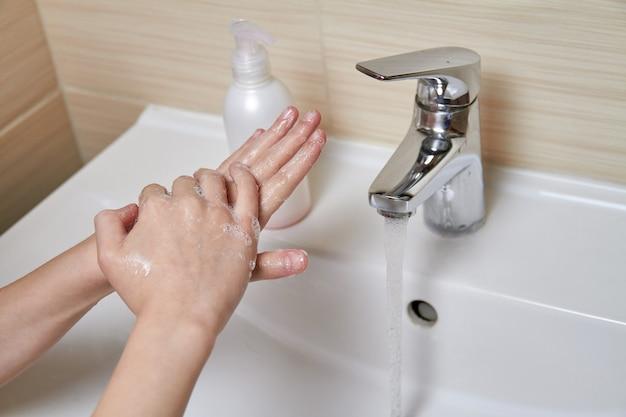 Uma jovem garota está lavando as mãos com água e sabão. prevenção de doenças virais. closeup, foco seletivo