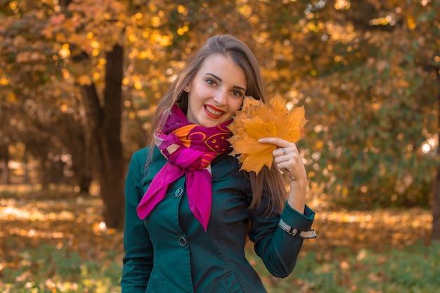 Uma jovem garota está no outono park e mantém as folhas nas mãos