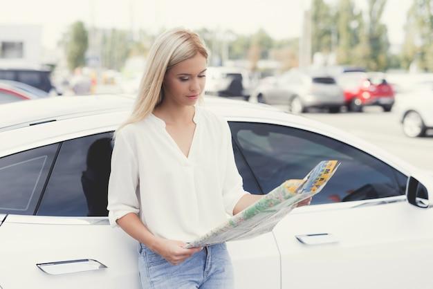 Uma jovem garota está olhando para um mapa de rodovias.