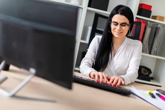 Uma jovem garota está sentada à mesa e digitando o texto no teclado.
