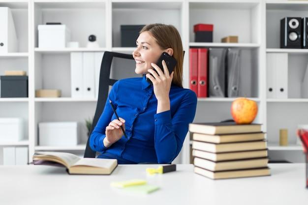 Uma jovem garota está sentada em uma mesa de computador, segurando um lápis na mão e falando ao telefone. antes que a menina jaz um livro aberto.