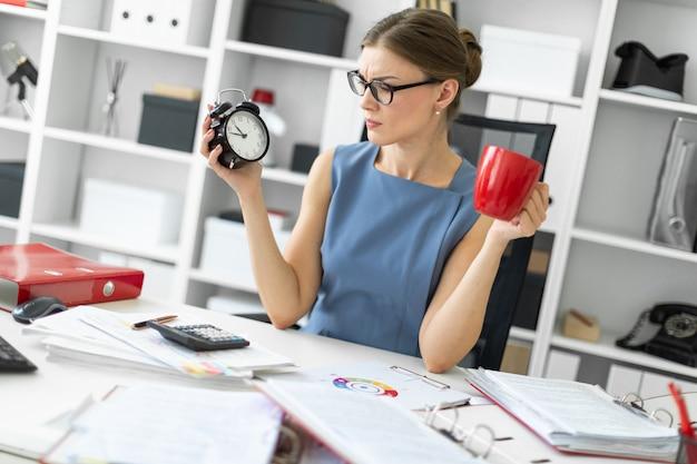 Uma jovem garota está sentada em uma mesa em seu escritório, segurando um despertador e um copo vermelho.