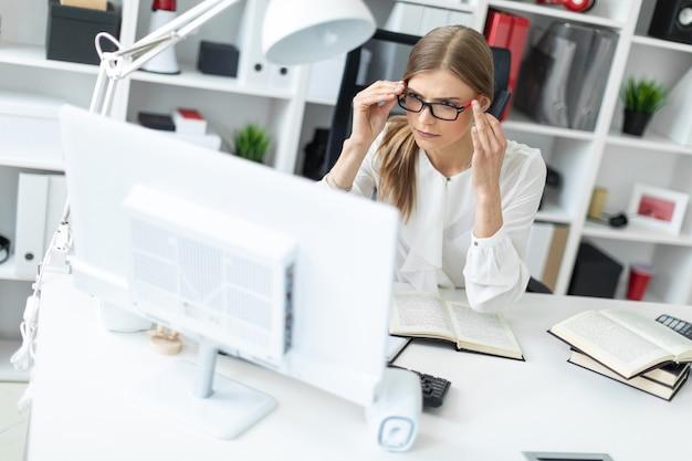 Uma jovem garota está sentada em uma mesa no escritório e colocando os óculos. antes que a menina jaz um livro aberto.