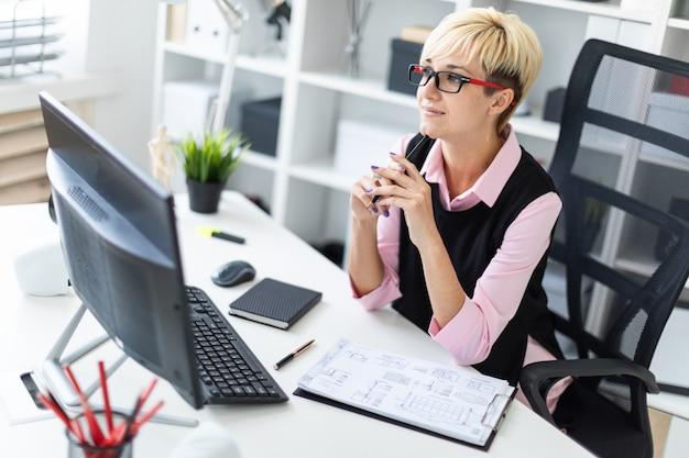 Uma jovem garota está sentada em uma mesa no escritório e encostou um lápis no queixo.