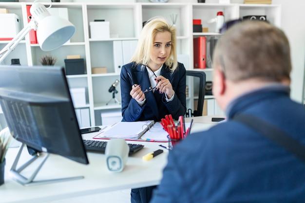 Uma jovem garota está sentada em uma mesa no escritório, segurando os óculos na mão e conversando com um homem.
