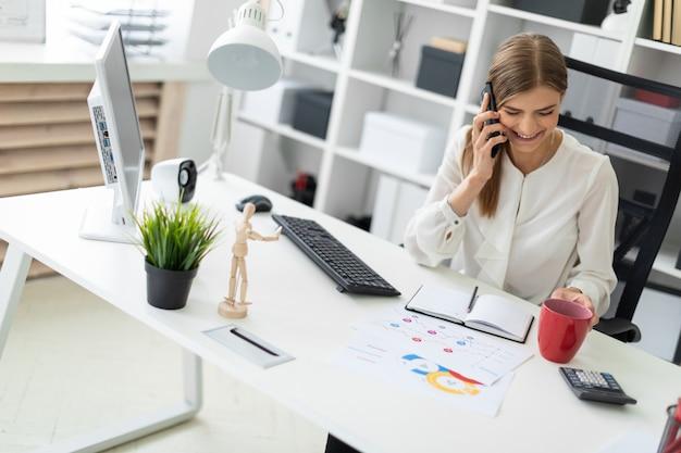 Uma jovem garota está sentada em uma mesa no escritório, segurando um copo vermelho na mão e falando ao telefone.