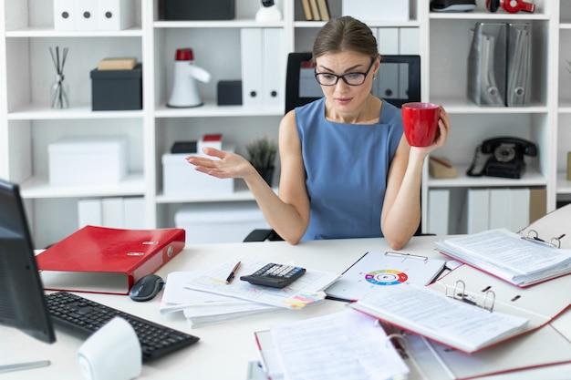 Uma jovem garota está sentada em uma mesa no escritório, segurando um copo vermelho na mão e trabalhando com documentos.