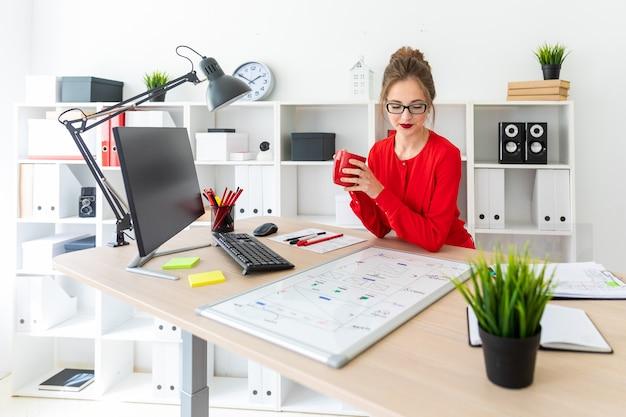 Uma jovem garota está sentada em uma mesa no escritório