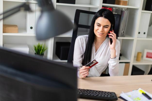 Uma jovem garota está sentada em uma mesa, segurando um cartão de banco na mão e falando ao telefone.