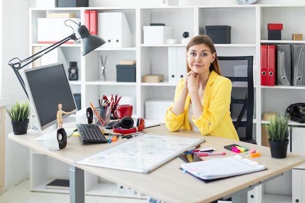 Uma jovem garota está sentada na mesa do computador. antes que a garota na mesa esteja um quadro magnético.