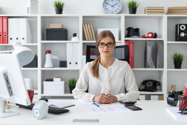 Uma jovem garota está sentada na mesa do computador no escritório.