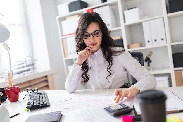 Uma jovem garota está sentada na mesa do escritório e está abençoando a calculadora.