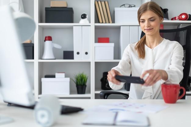 Uma jovem garota está sentada na mesa do escritório e tirando fotos no telefone.