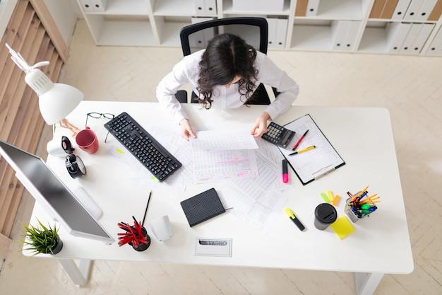 Uma jovem garota está sentada na mesa do escritório e trabalhando com documentos.