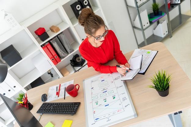 Uma jovem garota está sentada na mesa do escritório, segurando um marcador preto na mão e trabalhando com um bloco de notas. um quadro magnético está diante da garota.