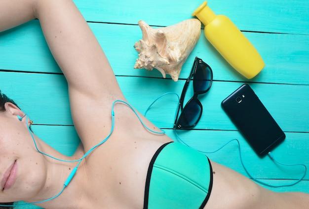 Uma jovem garota está tomando sol e ouvindo música através de fones de ouvido. os acessórios para o resort descansam na praia: protetor solar, óculos de sol, concha. vista do topo.