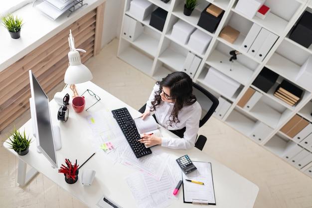 Uma jovem garota está trabalhando no computador no escritório e tem uma caneta e um caderno na mão.