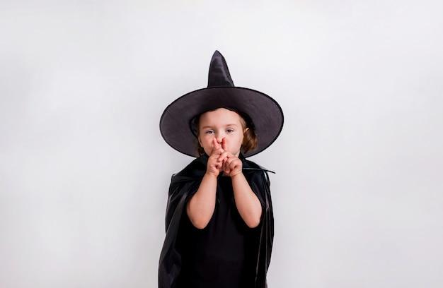 Uma jovem garota fantasiada de bruxa mostra as mãos em silêncio