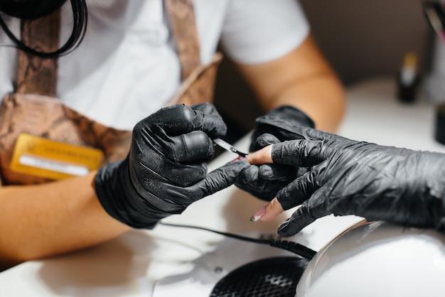 Uma jovem garota faz as unhas em close-up das mãos em um salão de beleza. salão de beleza.