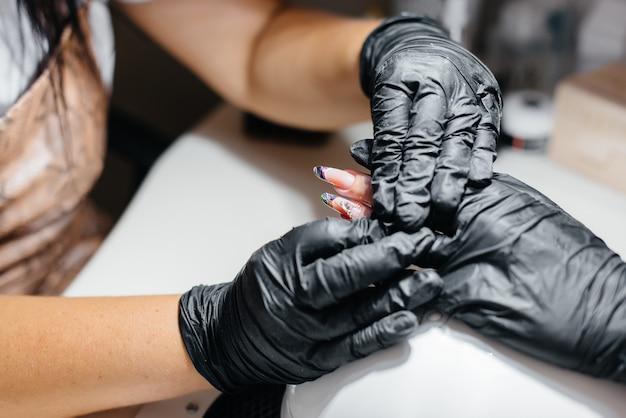 Uma jovem garota faz as unhas em close-up das mãos em um salão de beleza.