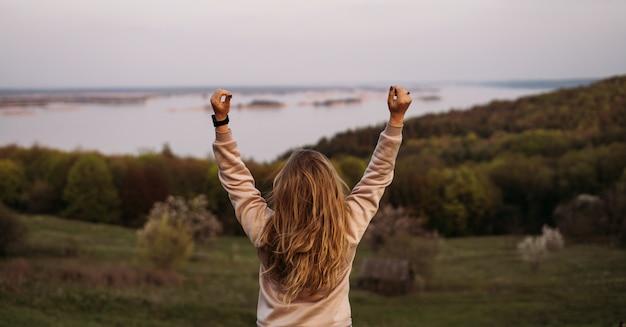 Uma jovem garota fica de costas com cabelos loiros e as mãos acima da cabeça.