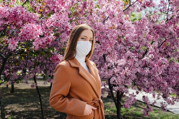 Uma jovem garota fica em um jardim florescendo usando uma máscara contra alergias e pandemias. alergia a flores.