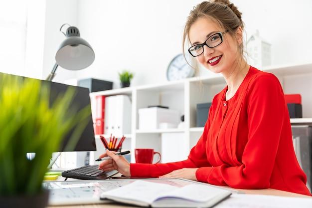 Uma jovem garota fica em uma mesa no escritório e detém um marcador preto na mão.